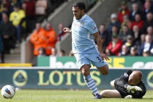 Tevez of Manchester City gets around Ruddy of Norwich City to score his hat trick during their English Premier League soccer match in Norwich