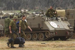 Israeli soldiers carry their gear past an armoured personel carrier as they head home near the border with Gaza