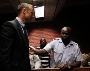 South African 'Blade Runner' Oscar Pistorius is escorted by police during his court appearance in Pretoria