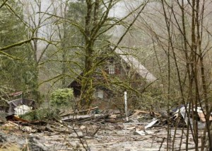 A home located off Highway 530 is surrounded by mud and debris as search work continues from a massive landslide that struck Oso near Darrington, Washington
