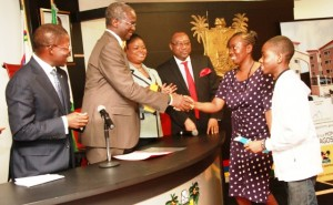 Governor, Babatunde Fashola presenting a key to the winner of the Shitta Scheme, Lagos HOMS, Mrs. Yetunde Oluwaseun and her son, Master Joseph Camille.