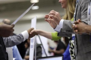 Corporate recruiters gesture and shake hands as they talk with job seekers at a Hire Our Heroes job fair targeting unemployed military veterans and sponsored by the Cable Show, a cable television industry trade show in Washington