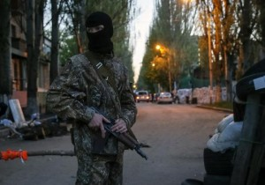 A pro-Russian armed man stands guard at a barricade near the state security service building in Slaviansk