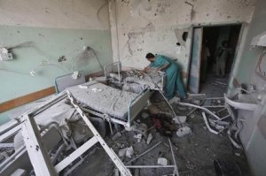 Palestinian medic inspects a damaged room at Al-Aqsa hospital, which witnesses said was damaged in Israeli shelling on Monday, in Deir El-Balah in the central Gaza Strip