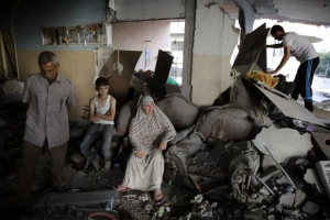 A Palestinian family gathers inside their damaged home, which police said was targeted in an Israeli air strike, in Gaza City
