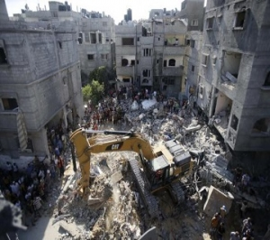 Palestinians gather as rescue workers search for victims under the rubble of a house in Rafah
