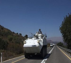 A member of UNDOF rides atop an armoured vehicle on Golan Heights