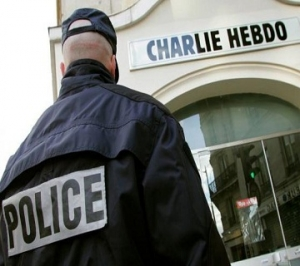 """File photo of a policeman standing guard outside the French satirical weekly """"Charlie Hebdo"""" in Paris"""