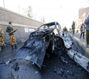 Policemen look at the wreckage of a car at the scene of a car bomb outside the police college in Sanaa
