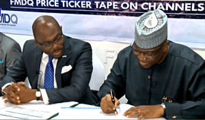 Executive Chairman/ CEO Channels Media Group, Mr. John Momoh signing the partnership agreement with The Managing Director and Chief Executive of the FMDQ OTC Securities Exchange, Mr Onadele Koko,
