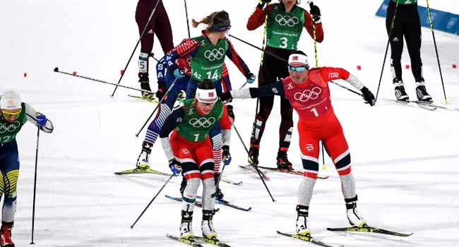 Norway's Maiken Caspersen Falla (2nd L) changes over with Norway's Marit Bjorgen as they compete during the women's cross country team sprint free final at the Alpensia cross country ski centre during the Pyeongchang 2018 Winter Olympic Games on February 21, 2018 in Pyeongchang. Jonathan NACKSTRAND / AFP