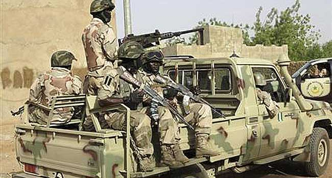 Nigerian soldiers hold their weapons as they sit on a military pick-up truck at their base in the town of Banamba