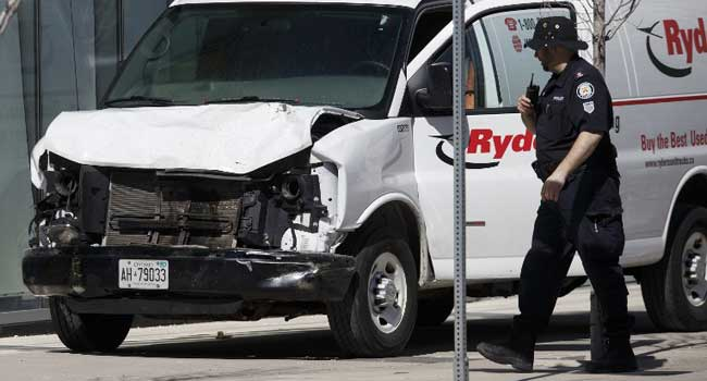 Police inspect a van suspected of being involved in a collision injuring at least eight people at Yonge St. and Finch Ave. on April 23, 2018 in Toronto, Canada. A suspect is in custody after a white van collided with multiple pedestrians. Cole Burston/Getty Images/AFP
