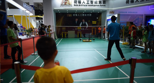 A robot plays badminton with a man at the 2018 World Robot Conference in Beijing on August 15, 2018. WANG Zhao / AFP