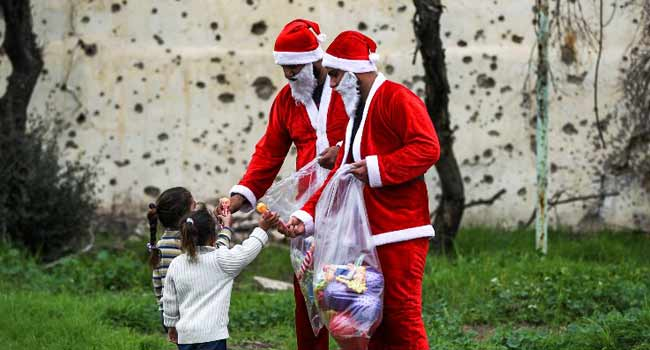 Iraqi Youths Dressed As Santa Distribute Gifts To Children In Mosul