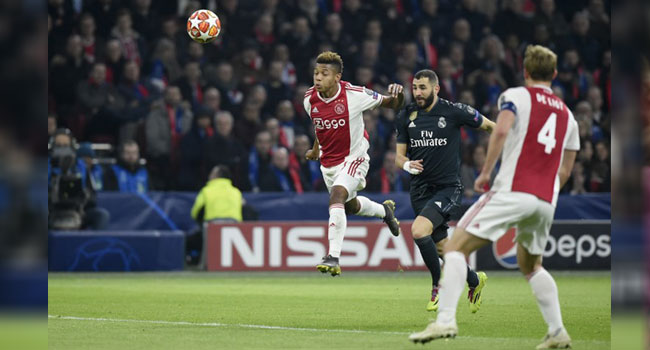 d6dbe10c48a Ajax s David Neres (L) and Real Madrid s Karim Benzema vie for the ball  during the UEFA Champions League round of 16 first leg football match  between Ajax ...