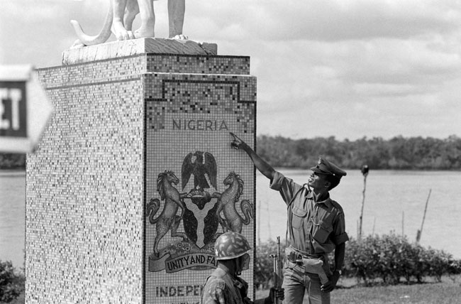 In this file photograph taken on November 13, 1967, a Nigerian federal army soldier points to a sign in Calabar, the oldest port on the West African coast, after the federal troops took the city from the Biafran rebellion, during the Biafran war. Colin HAYNES / AFP