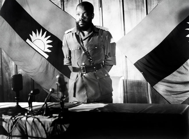 In this file photograph taken on August 16, 1967, Colonel Odumegwu Emeka Ojukwu, the leader of the breakaway Republic of Biafra, stands in front of a Biafra flag as he addresses a press conference in Enugu. AFP