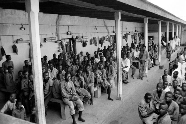 In this file photograph taken on November 1, 1967, Biafran prisoners and civilians wait at the federal camp of Nakurdi, a converted outdoor movie theatre in Enugu, after fighting between Nigerian federal army troops and the Biafran rebels, during the Biafran war. Colin HAYNES / AFP