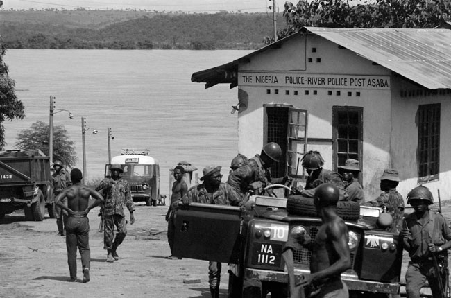In this file photograph taken on October 28, 1967, Nigerian federal army soldiers survey a police checkpoint on the west bank of the Niger River at Asaba, from where they launched an amphibian offensive on Biafra, during the Biafran war. Colin HAYNES / AFP