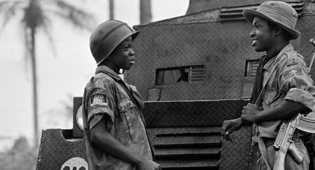 In this file photograph taken on August 31, 1968, a pair of child soldiers of the Biafran army, Moise, 14 (L) and Ferdinand, 16 (R) speak in Umuahia as the Nigerian federal troops continue their advance during the Biafran war. Francois Mazure / AFP