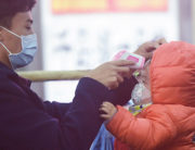 A staff member (L) checks body temperature of a child after a train from Wuhan arrived at Hangzhou Railway Station in Hangzhou, China's eastern Zhejiang province. STR / AFP