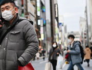 Pedestrians wearing protective masks to help stop the spread of a deadly virus which began in the Chinese city of Wuhan, walk on a street in Tokyo's Ginza area on January 25, 2020. CHARLY TRIBALLEAU / AFP