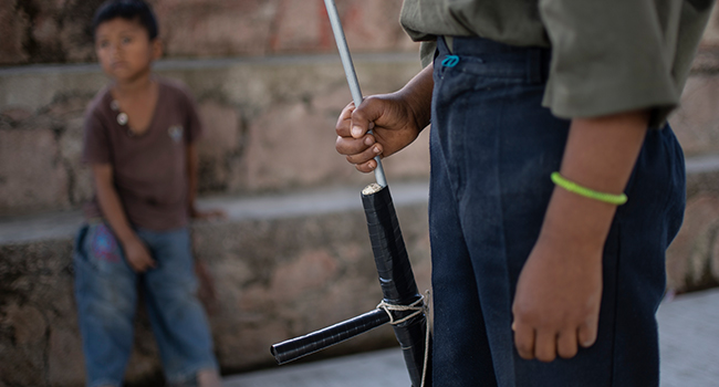 A boy aims a makeshift rifle as children are tought to use weapons by the Regional Coordinator of Community Authorities (CRAC-PF) community police force at a basketball court in the village of Ayahualtempan, Guerrero State, Mexico, on January 24, 2020. Pedro PARDO / AFP