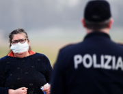 A resident wearing a respiratory mask (L) talks with a police officer giving informations at the entrance of the small town of Casalpusterlengo, southeast of Milan, on February 23, 2020. Miguel MEDINA / AFP