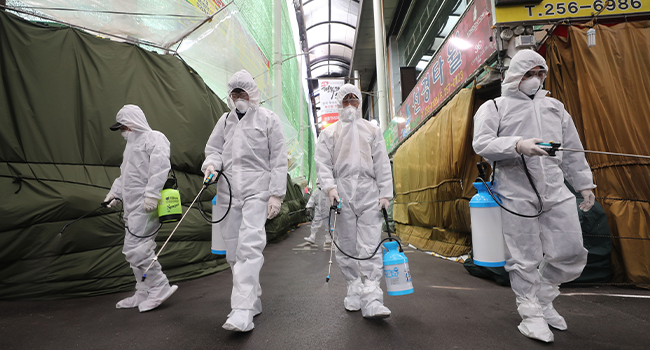 Market workers wearing protective gear spray disinfectant at a market in the southeastern city of Daegu on February 23, 2020 as a preventive measure after the COVID-19 coronavirus outbreak. YONHAP / AFP