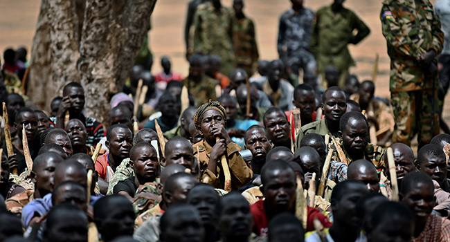 Trainee soldiers for a new unified army sit on the ground with their wooden rifles while attending a reconciliation programme run by the United Nations Mission in South Sudan (UNMISS) at a makeshift barracks in Mapel on January 31, 2020. TONY KARUMBA / AFP