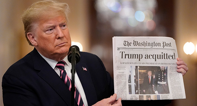 U.S. President Donald Trump holds a copy of The Washington Post as he speaks in the East Room of the White House one day after the U.S. Senate acquitted on two articles of impeachment, on February 6, 2020 in Washington, DC. Drew Angerer/Getty Images/AFP