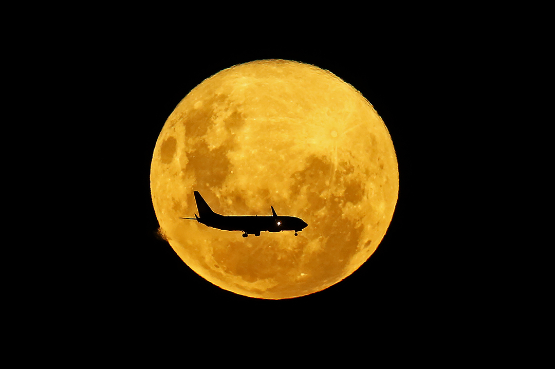 A plane passes in front of the full moon as seen from Curitiba, Brazil on March 9, 2020. - The supermoon is visible as the full moon coincides with the satellite in its closest approach to Earth, which makes it appear brighter and larger than other full moons. Photo: Heuler Andrey / AFP