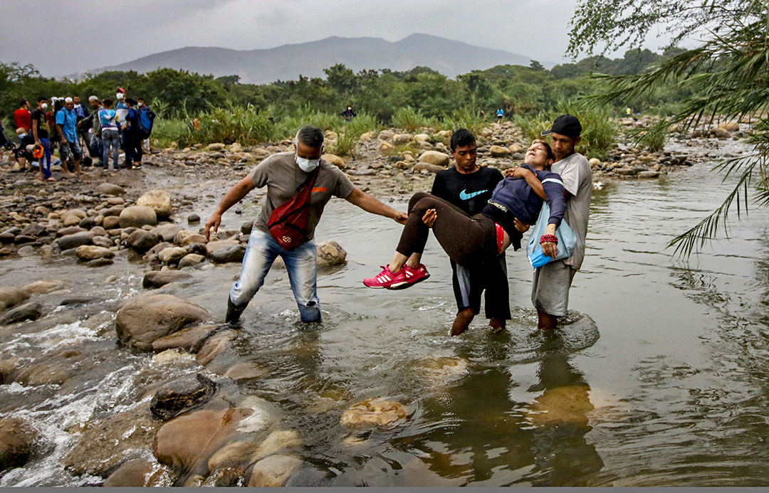 Venezuelan citizens wearing protective face masks to prevent the spread of Coronavirus carry an unconscious lady as they try to enter to Colombia, in Cucuta, Colombia, on March 14, 2020. - Colombian President Ivan Duque announced on Friday, March 13, 2020, the closure of all border crossings with Venezuela, and restricted the entry of foreigners who have been in Europe and Asia in the last 14 days, as measures to stop the expansion of the new Coronavirus. Photo: AFP