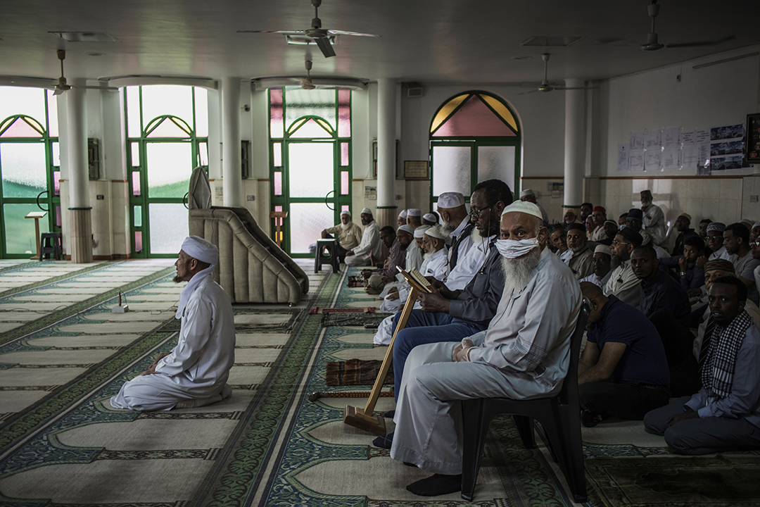 A Muslim man wearing a makeshift mask as a preventive measure against the COVID-19 coronavirus sits with other worshippers the beginning of the Friday prayer at the 23rd Street Mosque in the predominantly Muslim neighbourhood of Mayfair, Johannesburg, on March 20, 2020. - The mosque implemented a double shift prayer schedule to respect the instructions given by the South African Government limiting to 100 hundred the number of people per religious gathering. Photo: AFP