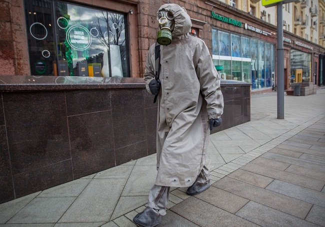 A man wears a protective suit and a gas mask as he walks along a street in central Moscow on March 21, 2020