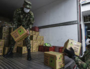 Members of Colombian army wear face masks agaisnt the spread of the new coronavirus as they unload milk boxes from a truck to be delivered at a childcare center in Bogota on March 21, 2020. Juan BARRETO / AFP