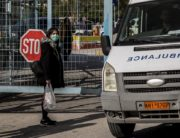 A woman wearing a protective face mask stands out of the Attikon University Hospital in Athens on February 27, 2020. - The Greek health ministry said a boy whose 38-year-old mother is already hospitalised with the virus after returning from a trip to northern Italy where there are several cases of the virus had also tested positive in Thessaloniki. The boy's school in Thessaloniki will be shut for two weeks and his entire class will stay at home, the school's principal told state TV ERT. (Photo by Angelos CHRISTOFILOPOULOS / AFP)