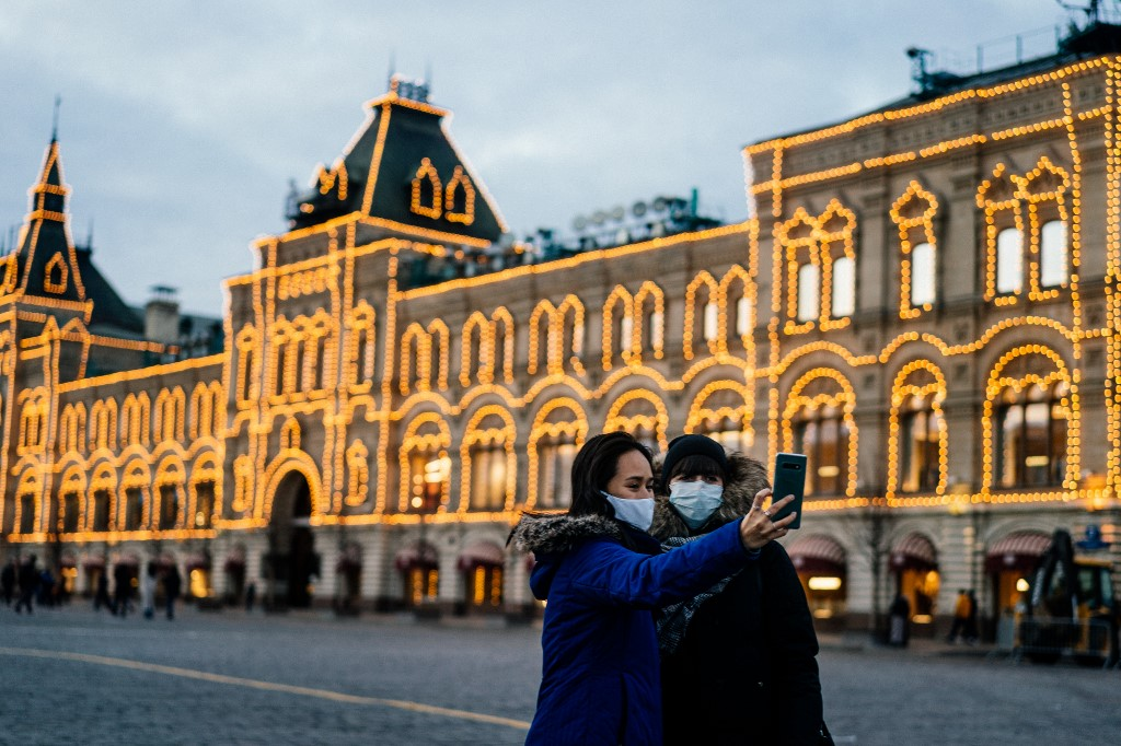 Two women wearing protective face masks to protect from the novel coronavirus, COVID-19, use their smartphone to take a selfie while standing on Red Square in downtown Moscow on March 18, 2020. Dimitar DILKOFF / AFP