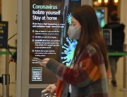 A notice warning people of the Coronavirus, is displayed as a passenger wearing a protective face mask passes through the Eurostar terminal at St Pancras International station in central London on March 17, 2020. JUSTIN TALLIS / AFP