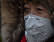 A woman wearing a face mask walks on the promenade of the Bund in Shanghai on March 8, 2020. Hector RETAMAL / AFP