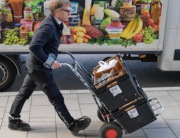 A worker delivers grocery bags to households in Stockholm, Sweden, on March 21, 2020 as internet shopping of food stuffs have skyrocketed in Sweden since the start of the Coronavirus Covid-19 outbreak. Anders WIKLUND / TT NEWS AGENCY / AFP