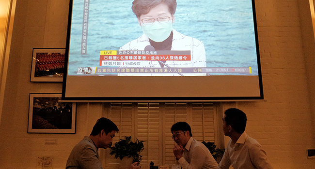 Friends have a drink as a projection is shown of a live press conference held by Chief Executive Carrie Lam, wearing a face mask as a precautionary measure against the COVID-19 coronavirus, in Hong Kong on March 23, 2020. Anthony WALLACE / AFP