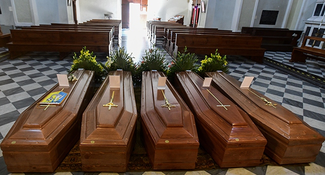 This picture taken on March 21, 2020 shows coffins on the ground of the church in Serina, near Bergamo, northern Italy. Italy on March 21 reported 793 new coronavirus deaths, a one-day record that saw the country's toll shoot up to 4,825, the 38.3 percent of the world's totality. Piero Cruciatti / AFP