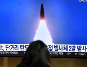 A woman watches a television news broadcast showing a file image of a North Korean missile test, at a railway station in Seoul on March 21, 2020. Jung Yeon-je / AFP