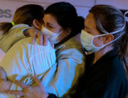 Healthcare workers dealing with the new coronavirus crisis in Spain, hug each other as they are cheered on by people outside La Fe hospital in Valencia on March 26, 2020.