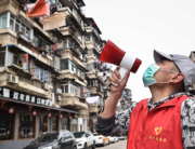 A community volunteer informs residents to get vegetables with a loudspeaker in Wuhan, in China's central Hubei province on March 13, 2020. STR / AFP