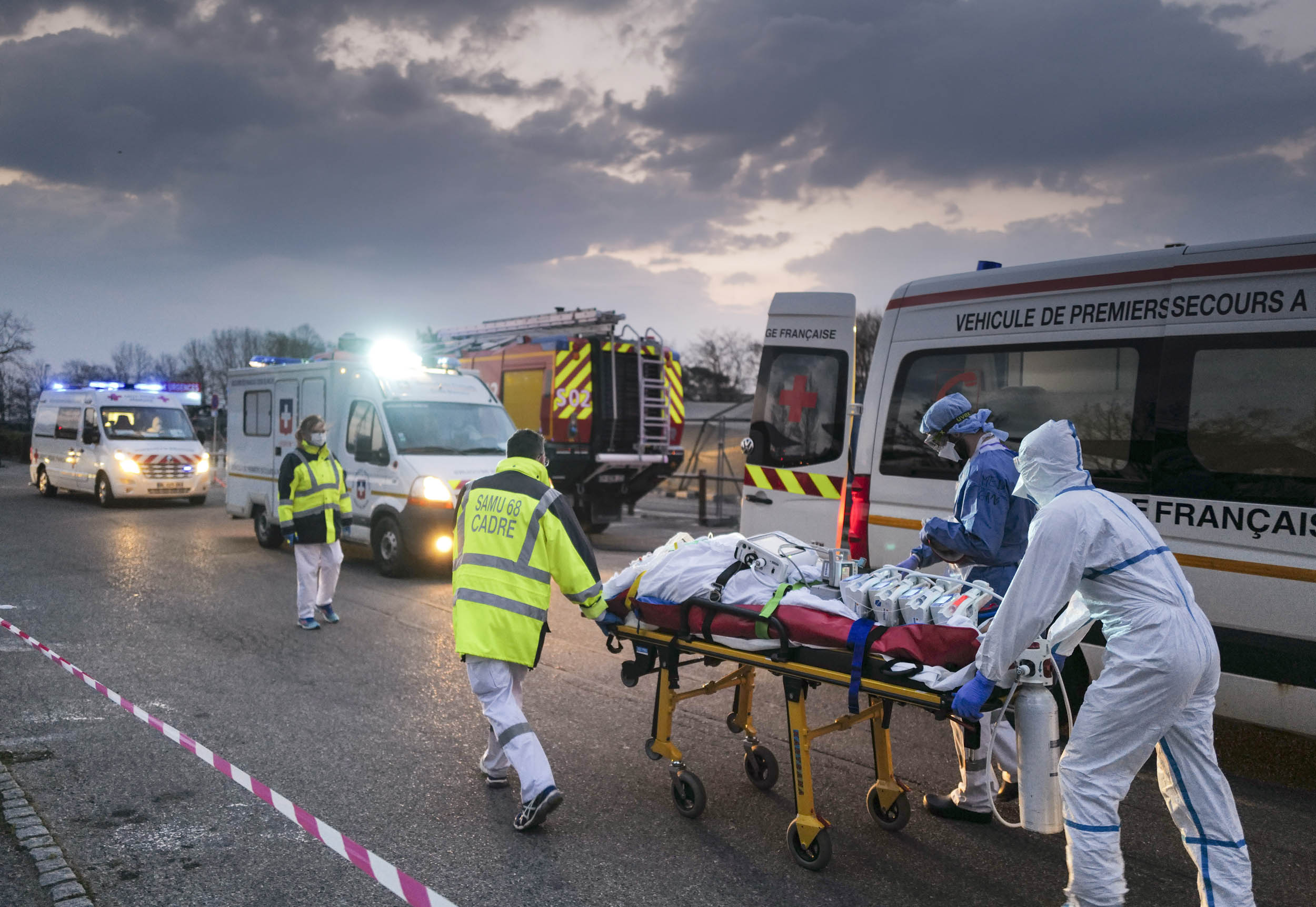 Emergency medical personnel carries a patient affected with coronavirus (Covid-19) from a military hospital to an ambulance before being transported aboard a medicalised TGV (high-speed train) to be evacuated towards hospitals of other French regions on March 29, 2020 in Mulhouse, eastern France, amid the spread of the COVID-19 (new coronavirus) pandemic. Photo: Sebastien Bozon / AFP