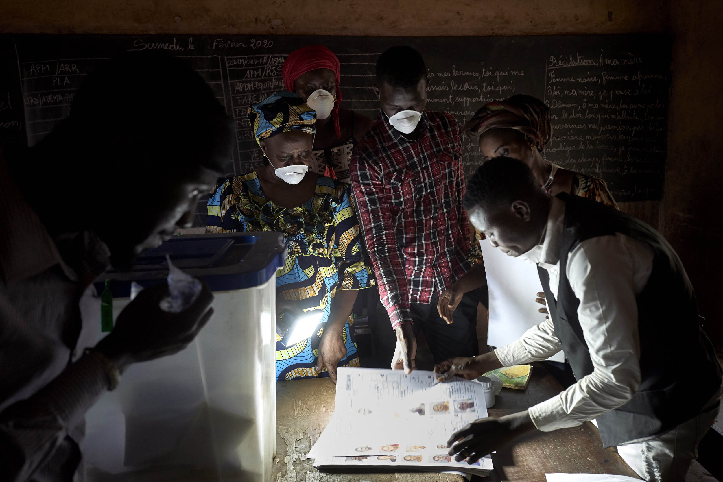 Electoral officials wearing masks as a preventive measure against the spread of the COVID-19 coronavirus count the votes at a polling station in Bamako on March 29, 2020. - Malians headed to the polls on March 29, 2020, for a long-delayed parliamentary election just hours after the country recorded its first COVID-19 coronavirus death and with the leading opposition figure kidnapped and believed to be in the hands of jihadists. Photo: Michele Cattani / AFP