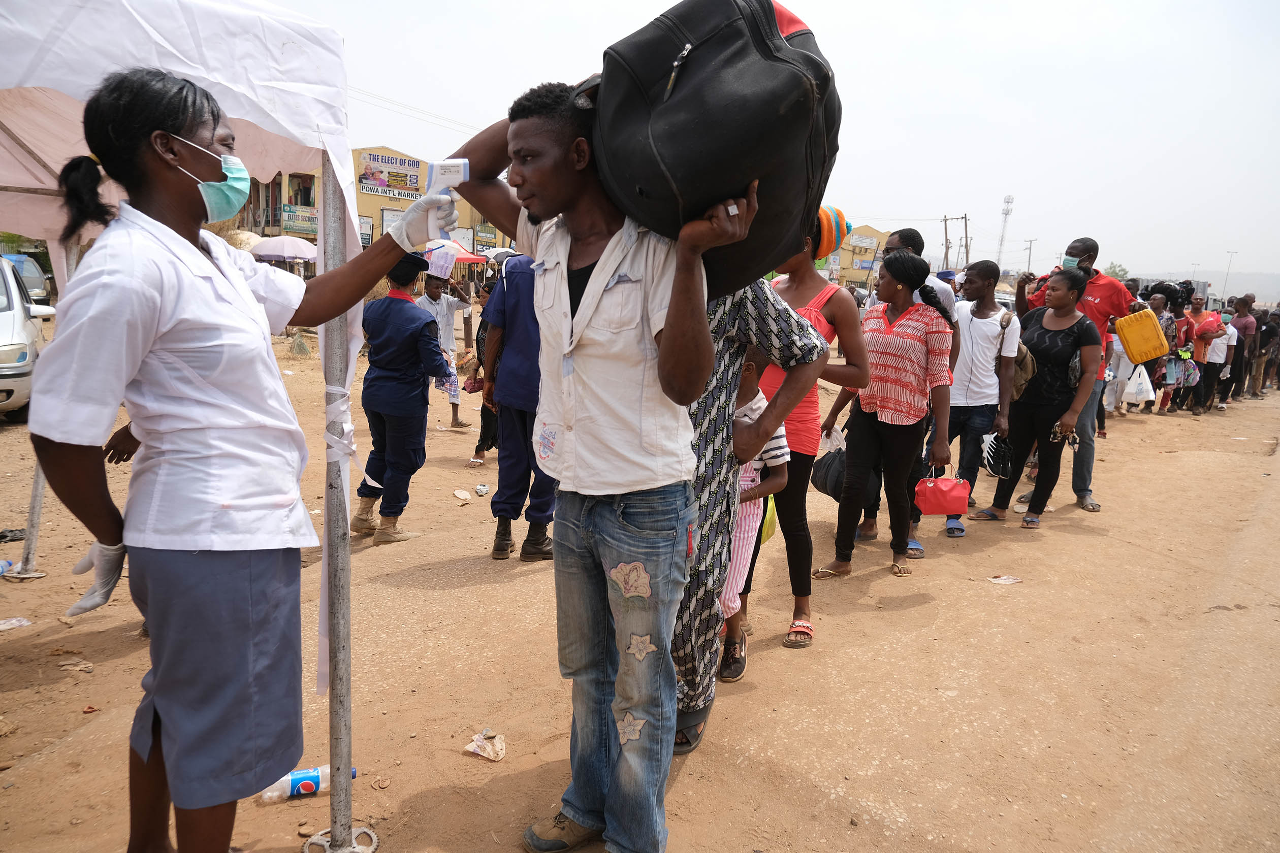 People queue to have their temperatures checked at a border-end of Abuja, as the authorities try to limit the spread of the coronavirus disease (COVID-19) in Abuja, Nigeria March 30, 2020. Photo: Sodiq Adelakun / Channels TV